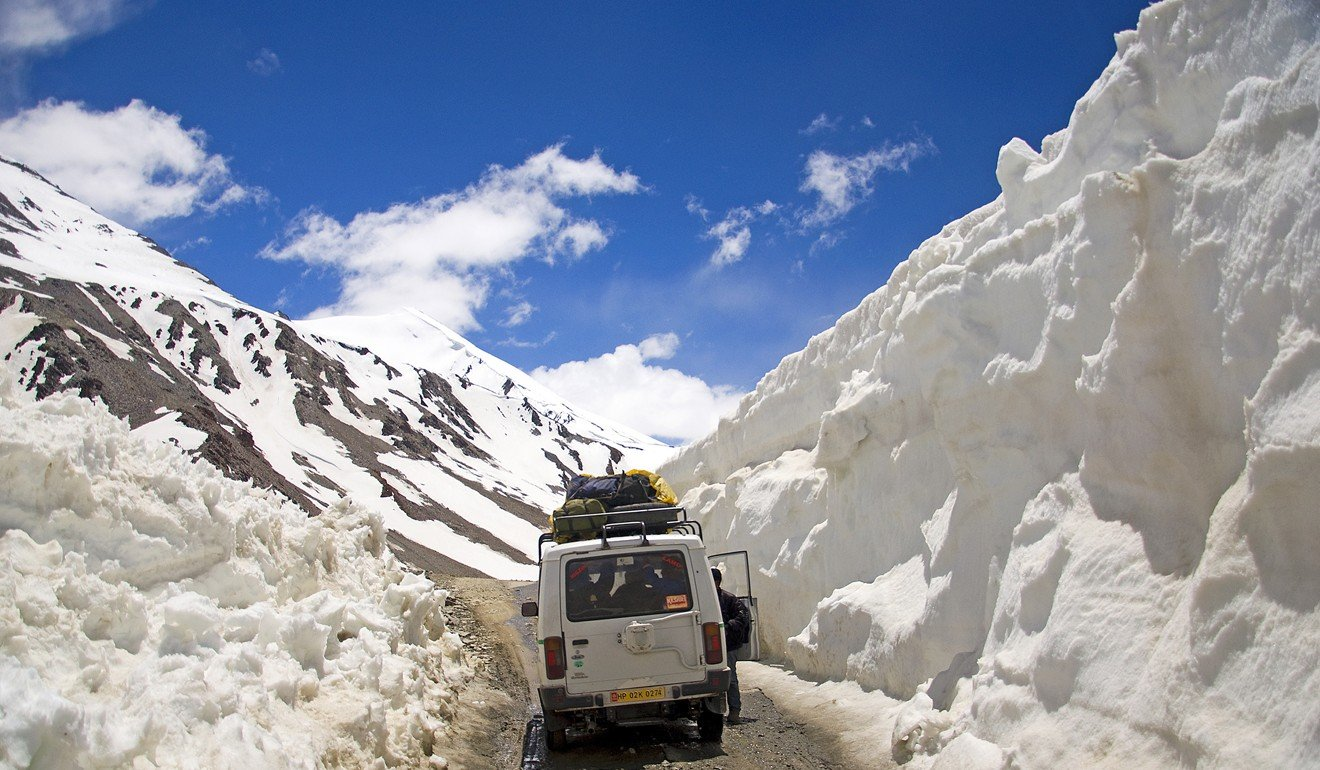 A van negotiates a road fringed by deep snow. Diminishing snowfall is evidence of the impact of climate change in Ladakh. Photo: Tim Pile