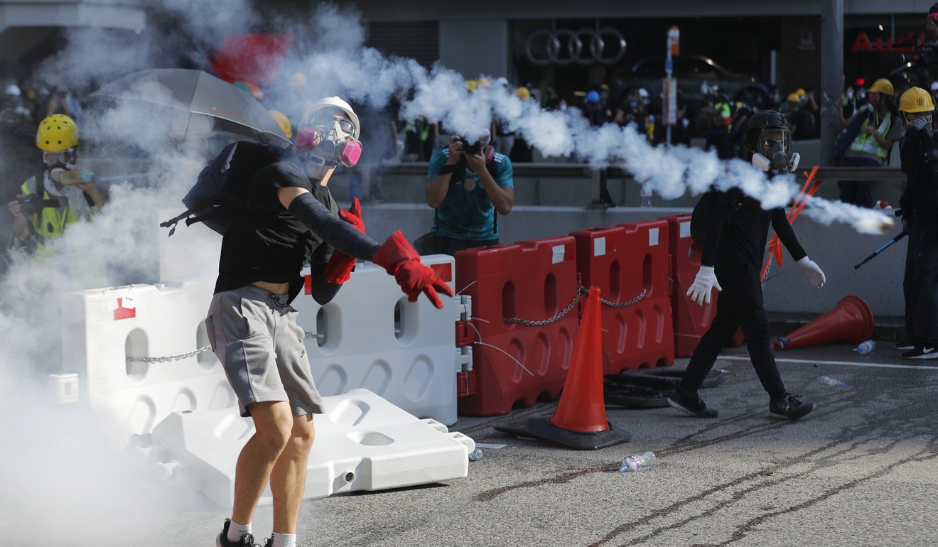 A protester throws back a tear-gas canister during demonstrations in Hong Kong. Photo: AP