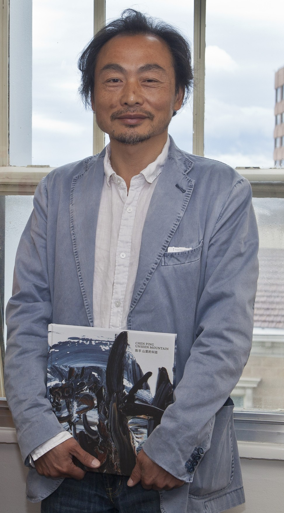Chen with his book of paintings about Chinese tin miners in Tasmania. Photo: Tamara Thiessen