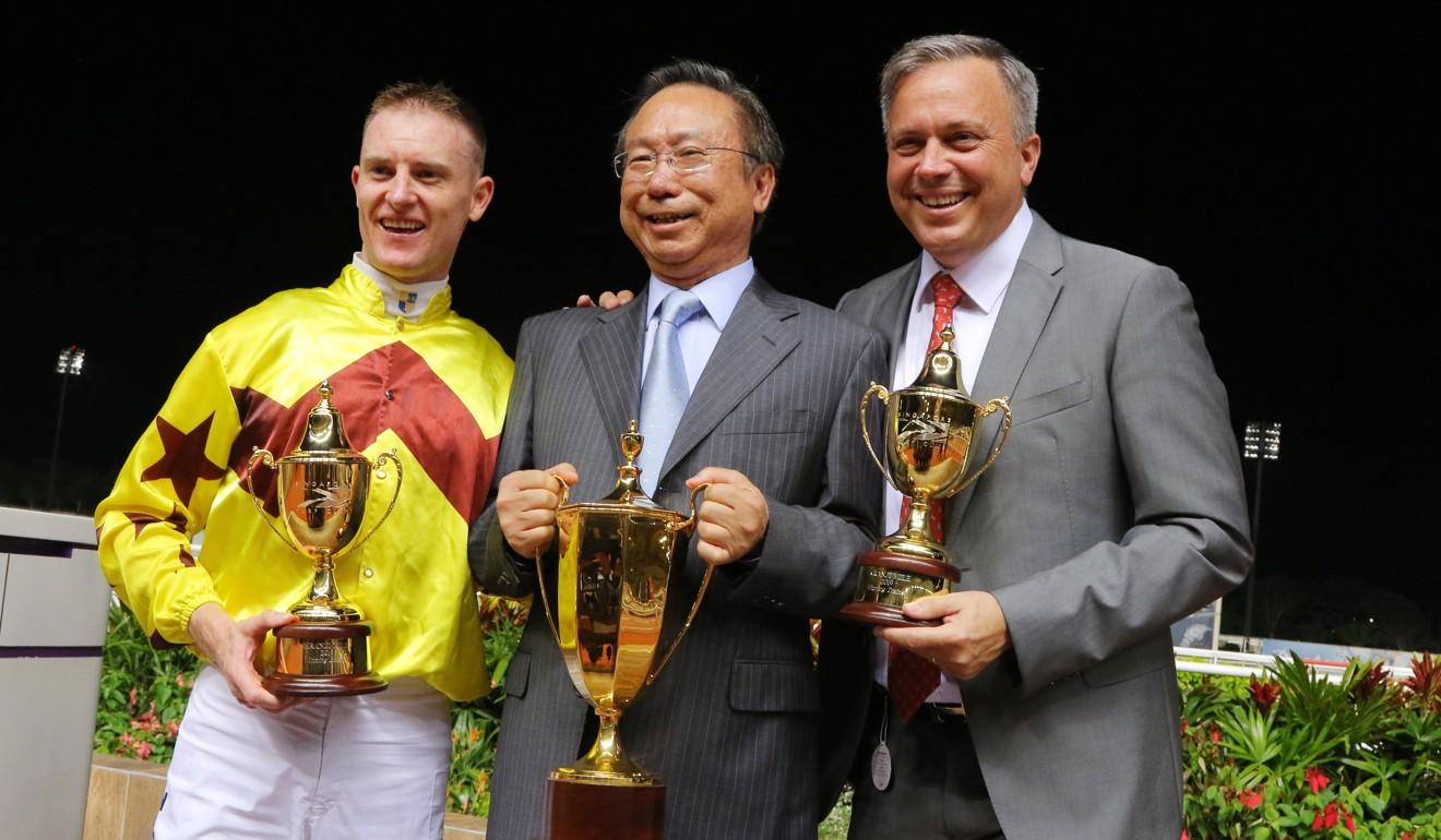 Jockey Zac Purton celebrates the win of Southern Legend with owner Boniface Ho in Singapore.