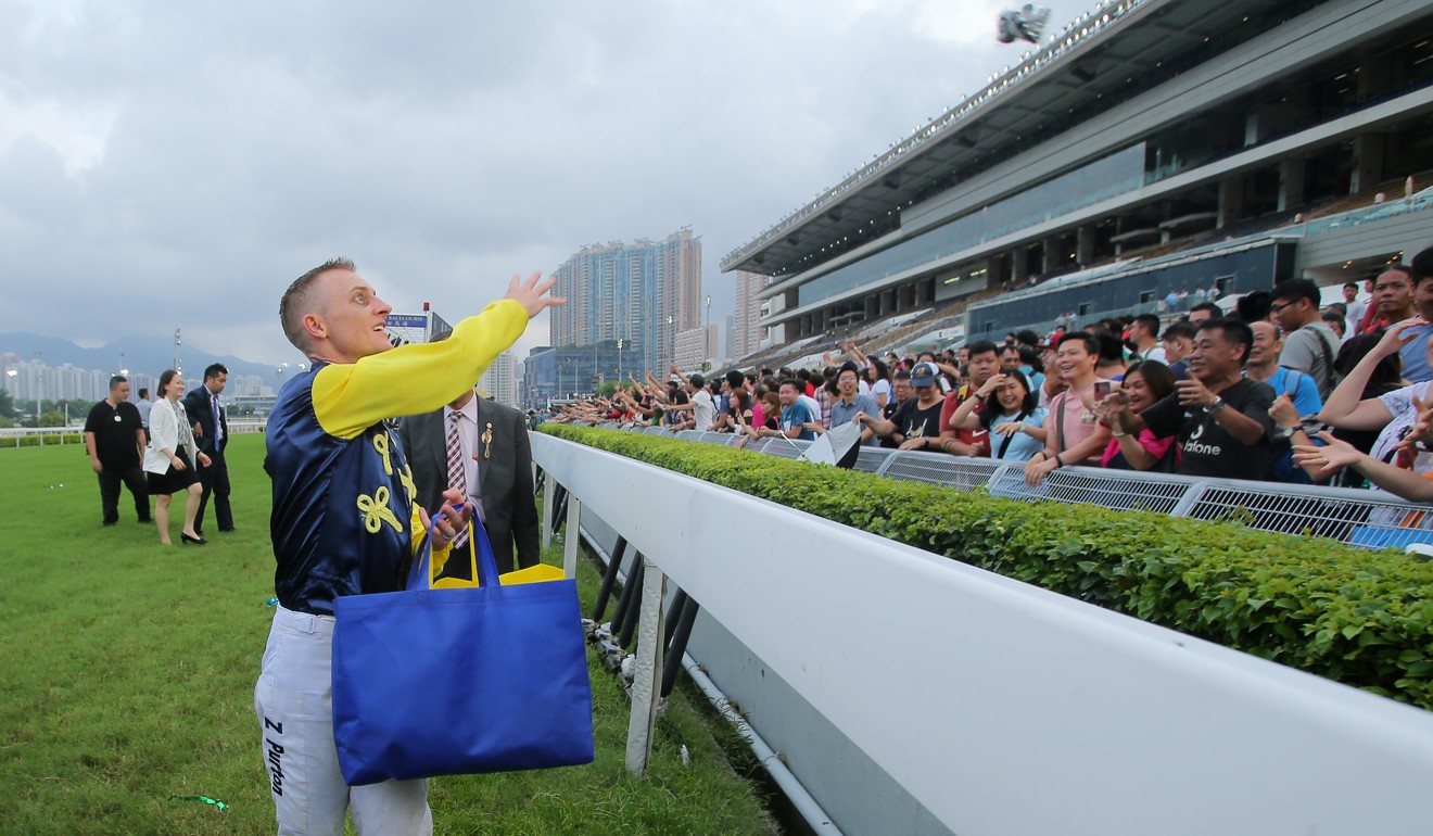 Zac Purton throws souvenirs to the crowd after being crowned last season's champion jockey.