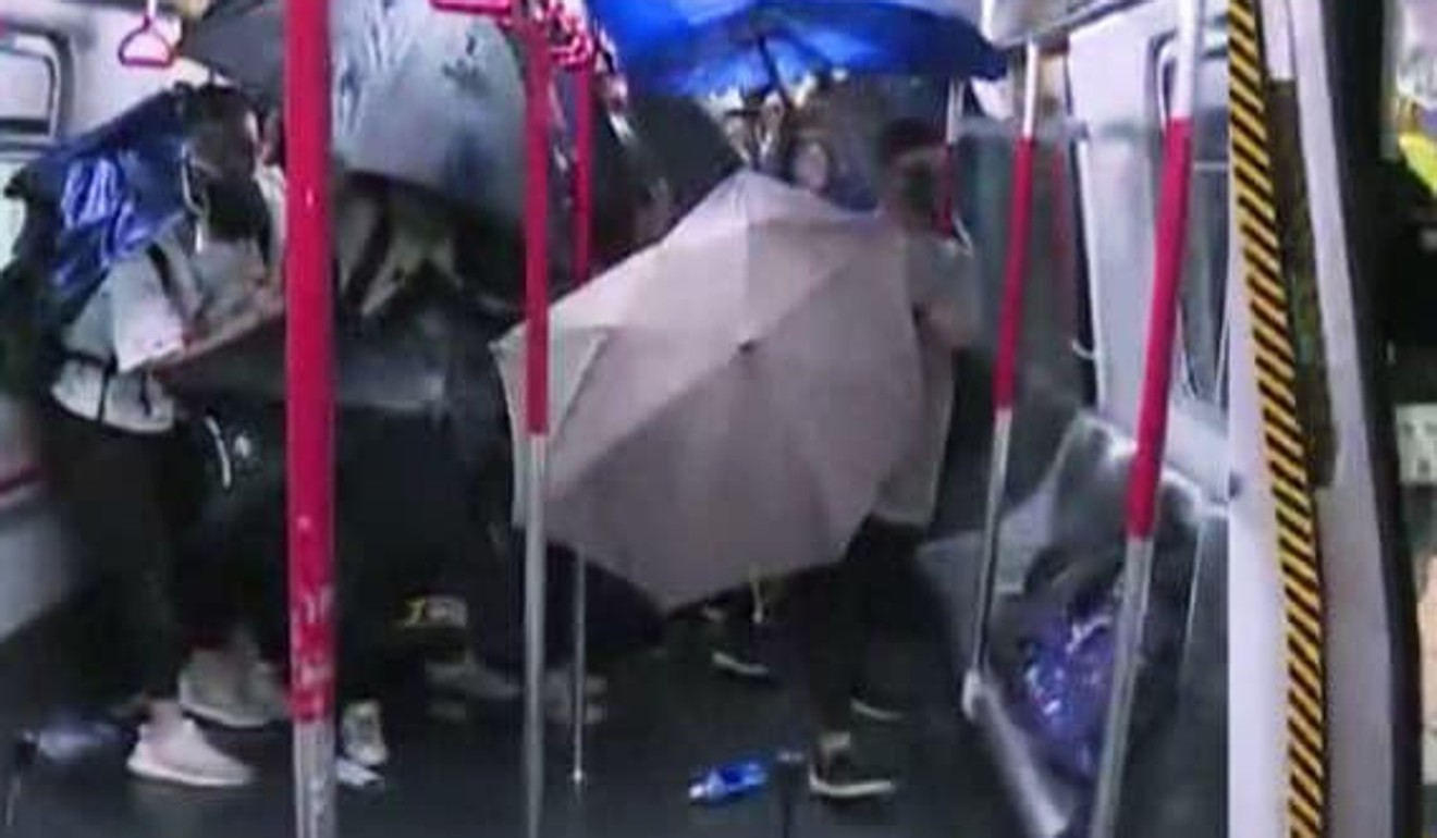 Passengers open their umbrellas to protect themselves after 'raptors' stormed onto an MTR train and beat four commuters. Photo: TVB