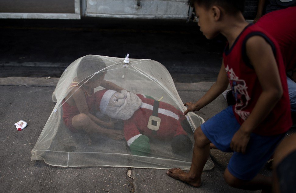 A boy plays underneath a mosquito net in Manila, the Philippines. Photo: AFP