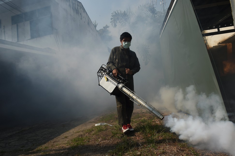 A municipal worker in Bangkok, Thailand, fumigates a residential area against the Aedes aegypti mosquito. Photo: AFP