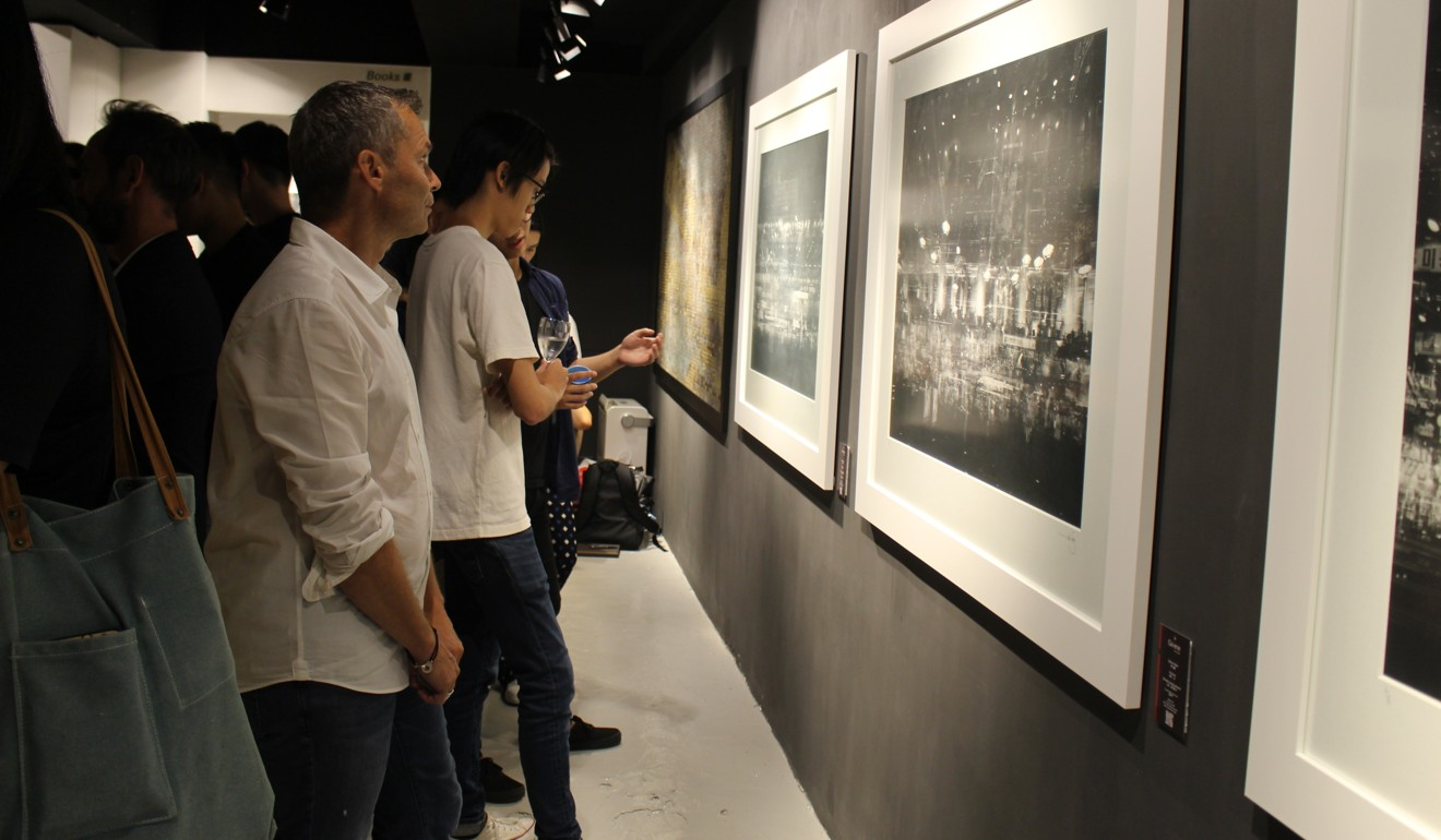 Visitors look at Wan's photos. Photo: Snow Xia