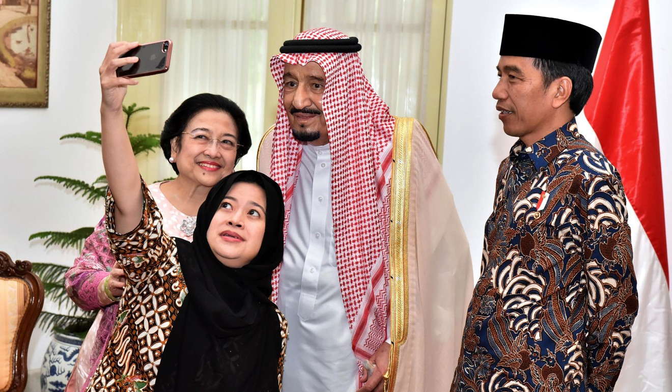 Indonesian President Joko Widodo looks on as his coordinating Minister of Human Development and Cultural Affairs Puan Maharani and her mother, former president Megawati Sukarnoputri, and Saudi Arabia's King Salman take a selfie at the Presidential Palace in Jakarta. Photo: AFP