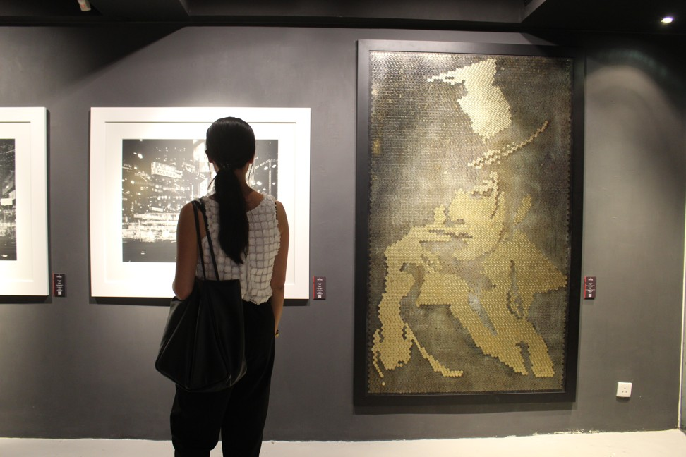 A visitor views Simon Wan's photography (left) and a Giraffe Leung artwork made from coins at La Galerie Paris 1839. Photo: Snow Xia