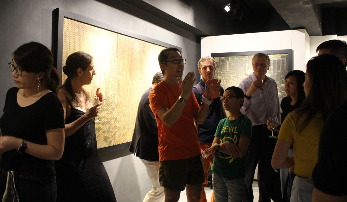 Wan (centre) explains the thinking behind his City Glow photography exhibition to visitors at La Galerie Paris 1839. Photo: Snow Xia