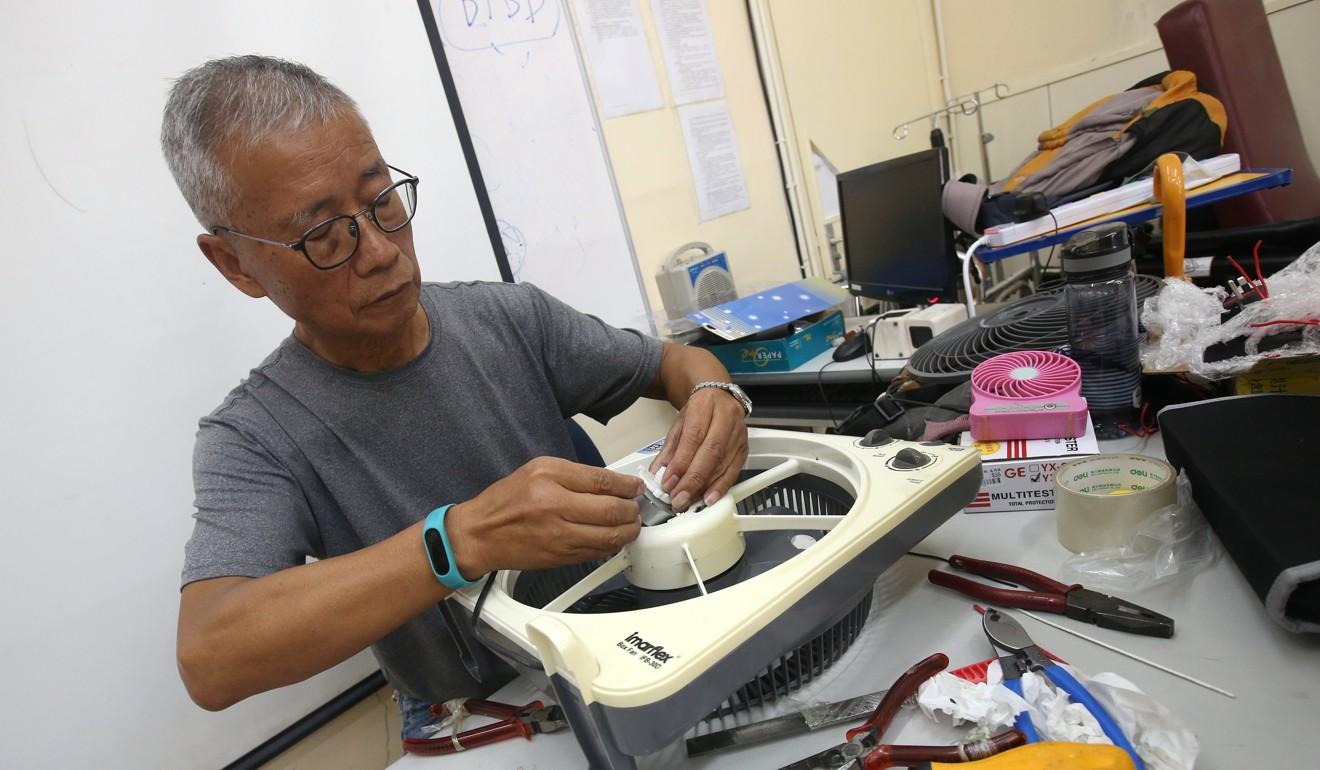Volunteer Wat Po-wing, 70, repairs an electric fan. Photo: David Wong