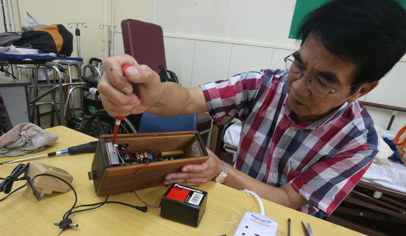 Siu repairs a radio at the Repair Cafe. Photo: David Wong