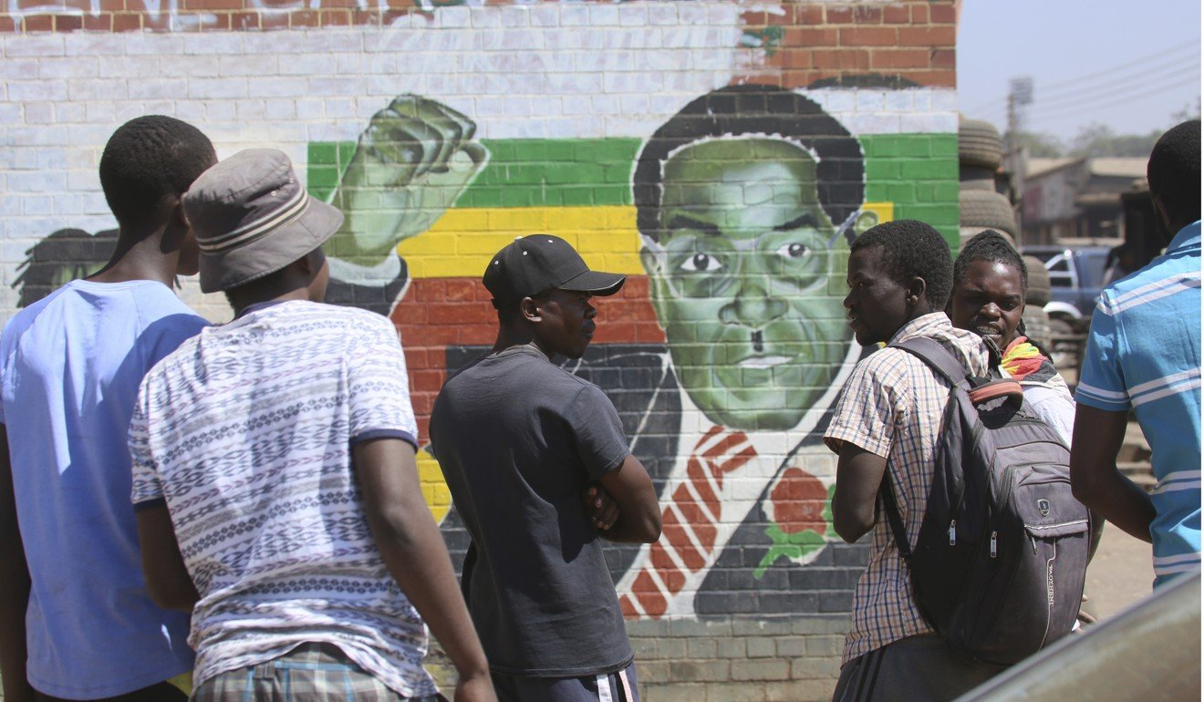 People gather around a portrait of Robert Mugabe in Harare on Friday. Photo: AP