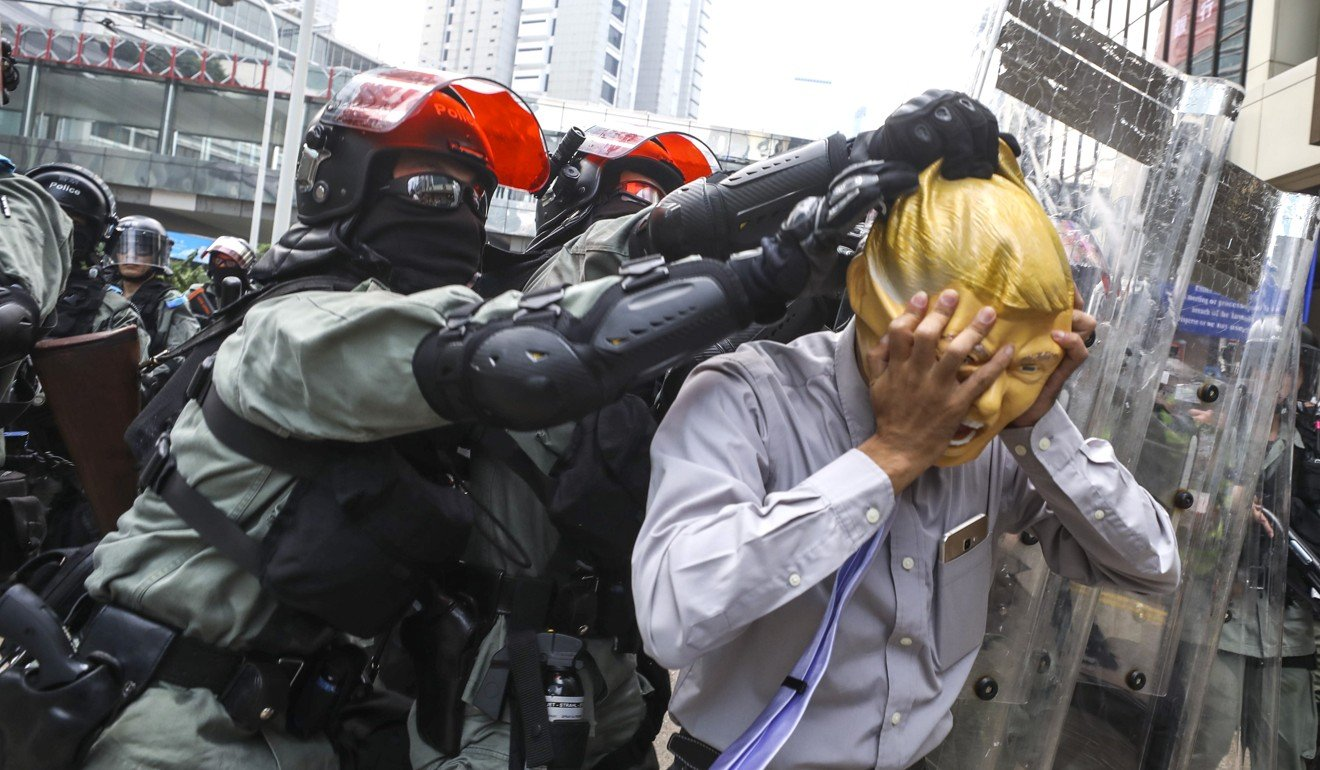 A police officer tries to remove a protester's Donald Trump mask during a march in Hong Kong. Photo: Dickson Lee