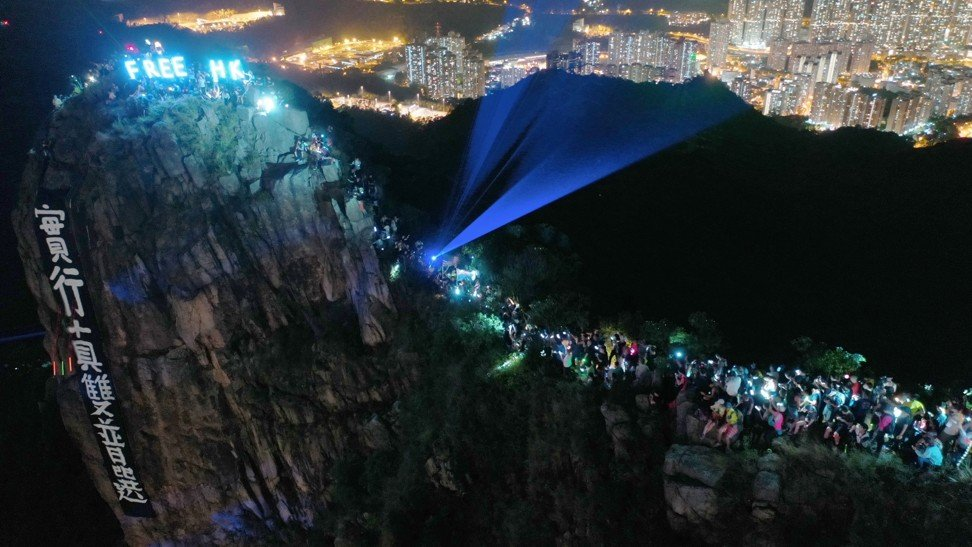 Protesters hang a banner calling for universal suffrage and form a human chain on Lion Rock, in protest against the now withdrawn extradition bill – an example of the trail community making their voices heard. Photo: Martin Chan