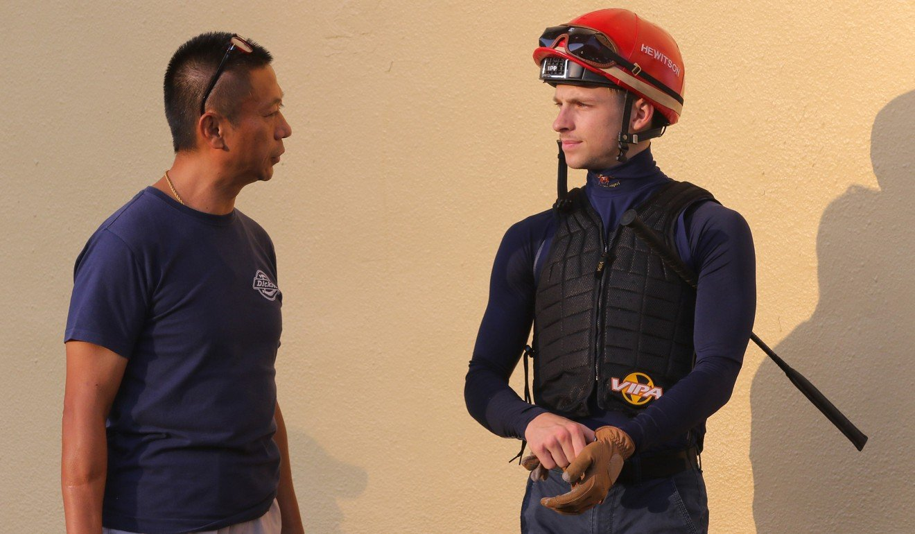 Trainer Danny Shum talks to jockey Lyle Hewitson.