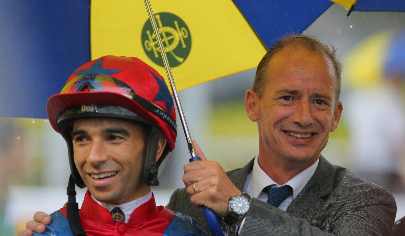 Richard Gibson celebrates a winner with jockey Joao Moreira.