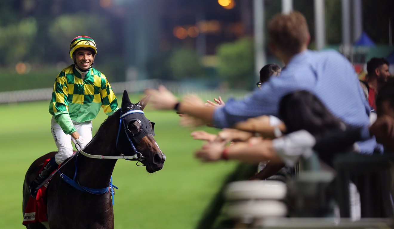 Joao Moreira high-fives the crowd after winning on Green Luck at Happy Valley.