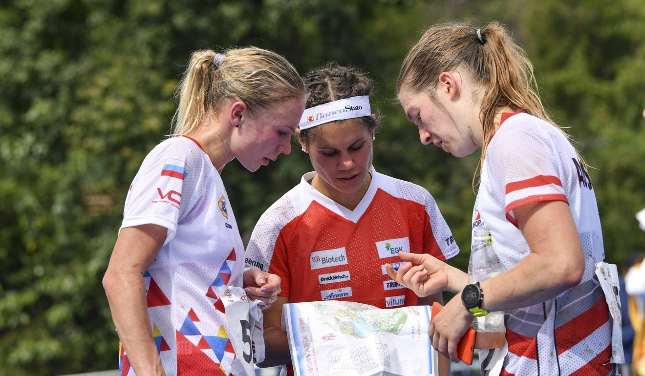 Gold medalist Anastasiia Rudnaia (left) of Russia, silver medalist Ursula Kadan (right) of Austria and bronze medalist Elena Roos of Switzerland communicate after finishing the individual long distance final of orienteering. Photo: Xinhua