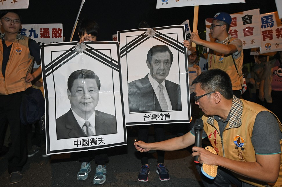 A Taiwanese independence activist sets fire to portraits of Xi and Ma during a demonstration in Taipei, in 2015. Photo: AFP