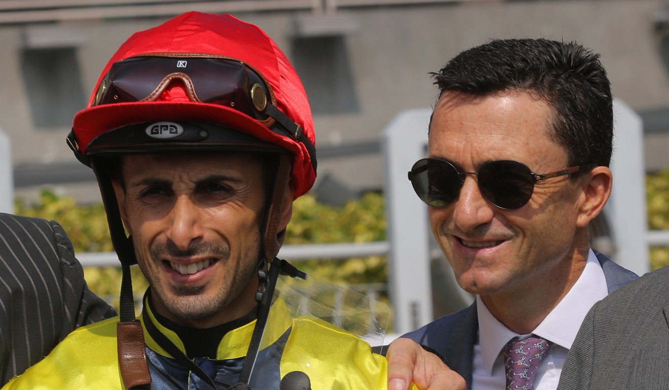 Jockey Alberto Sanna celebrates a winner with trainer Douglas Whyte at Sha Tin on Sunday.