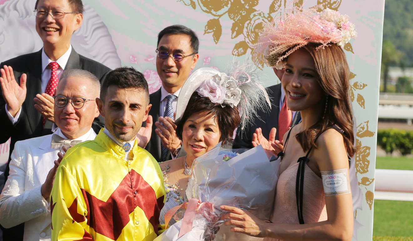 Kelly Cheung presents the trophy to jockey Alberto Sanna.