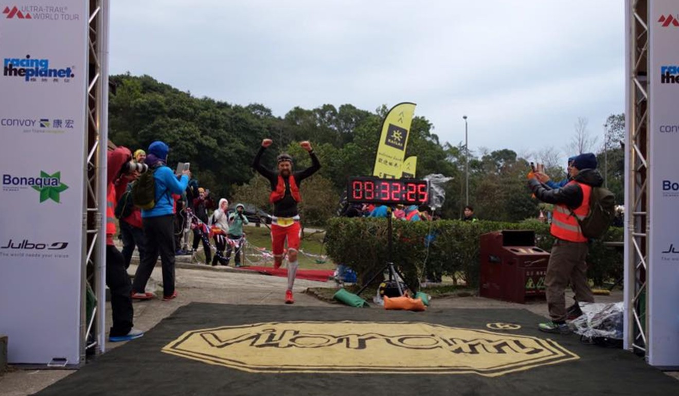 Francois d'Haene finishes the 2016 Vibram HK 100. The race was hit by very cold weather and Lin Jie stayed at her post for 40 hours to help runners. Photo: Bryon Powell/@iRunFar