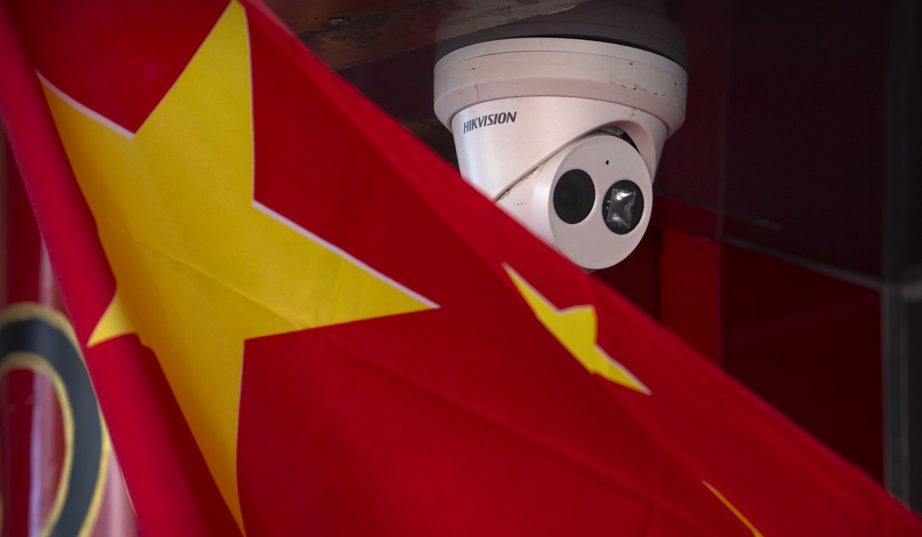 A Chinese flag hangs near a Hikvision security camera outside of a shop in Beijing, Tuesday, Oct. 8, 2019. Photo: AP