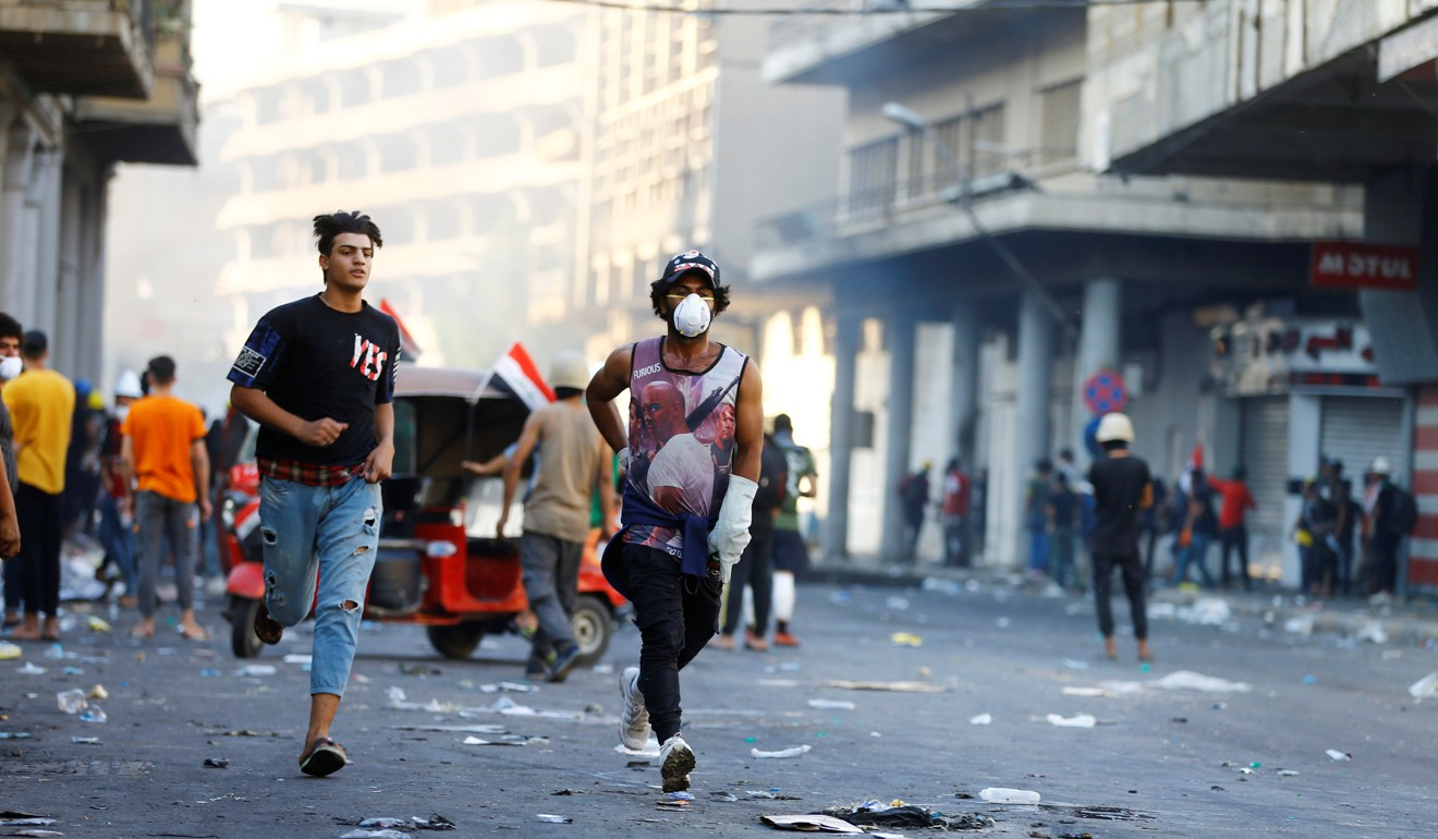 Demonstrators run during the ongoing anti-government protests in Baghdad. Photo: Reuters