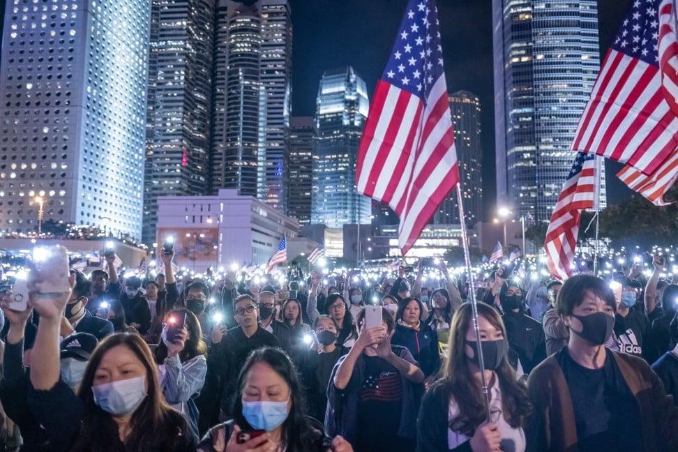 """Los manifestantes encienden luces desde sus teléfonos inteligentes mientras ondean banderas estadounidenses durante la """"Asamblea del Día de Acción de Gracias por la Ley de Derechos Humanos y Democracia de Hong Kong"""" en Hong Kong el 28 de noviembre. Foto: Bloomberg"""