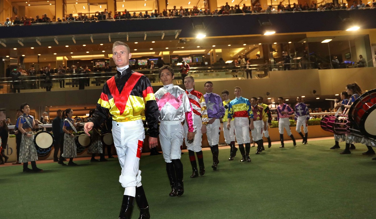 Jockeys enter the track for the IJC at Happy Valley.