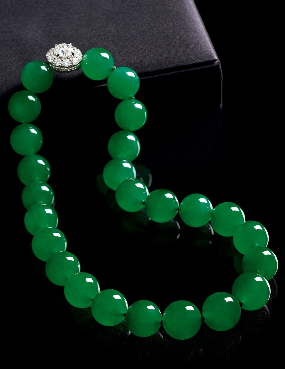 Graduated jadeite beads of vivid emerald green colour and very high translucency, with an 18ct gold clasp set with 5ct of diamonds