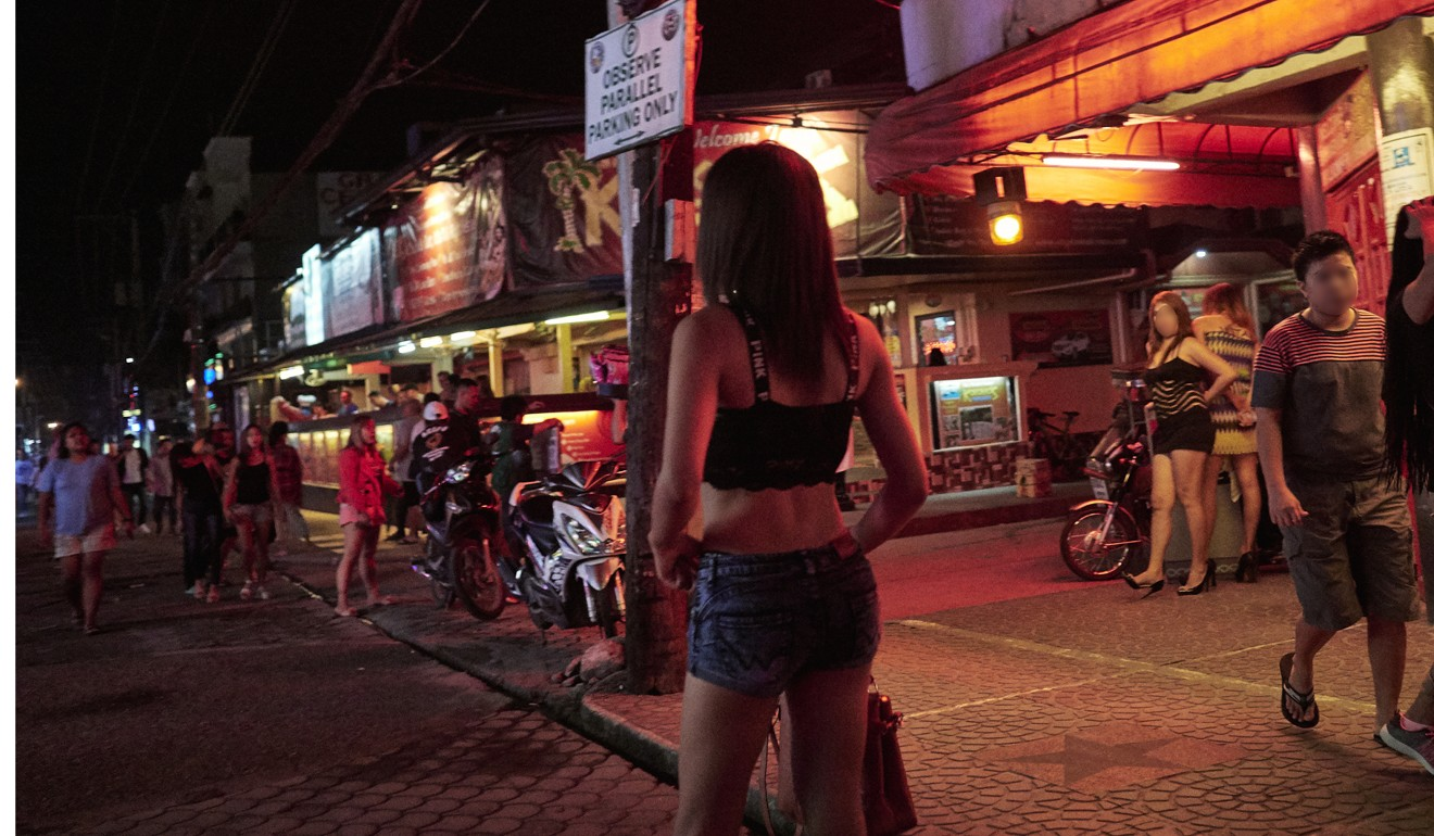 A young woman is seen walking on Fields Avenue - a pedestrianised street in Angeles City's red light district. Photo: Francesco Brembati