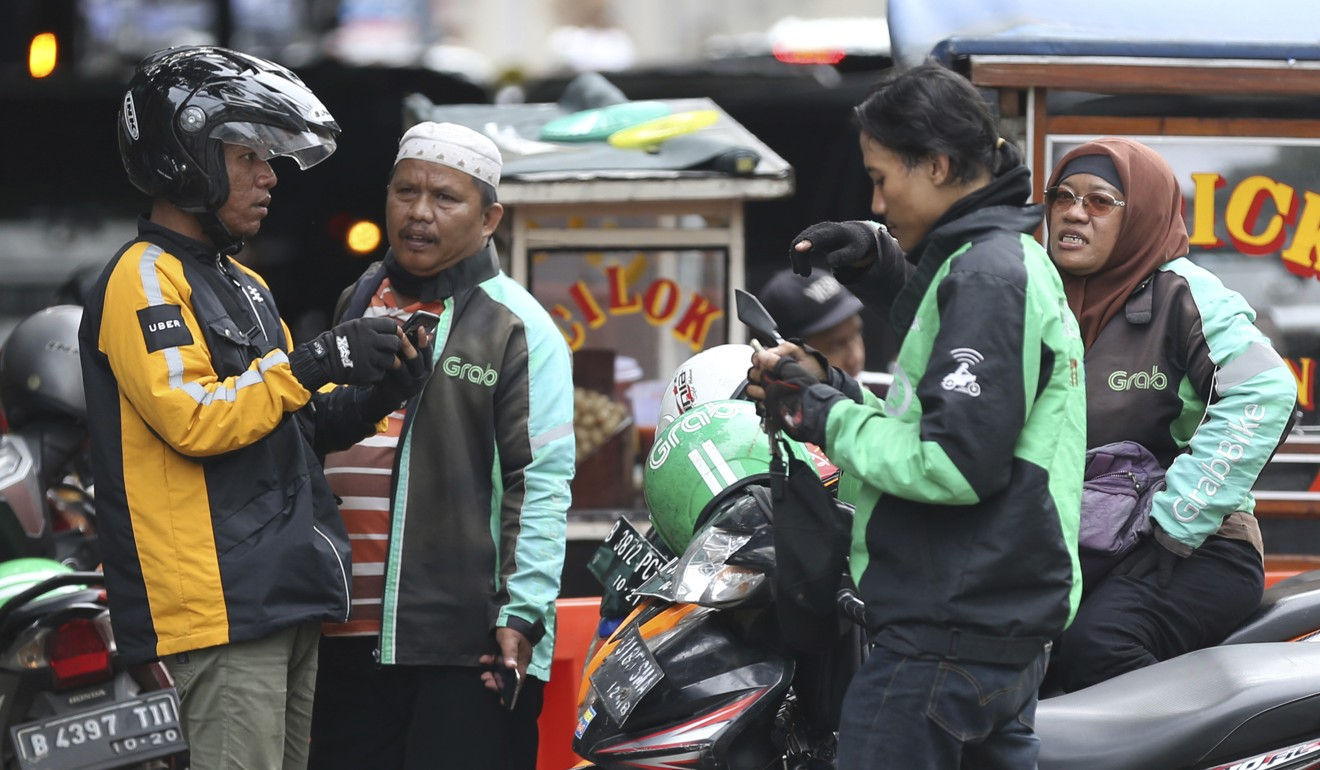 An Uber rider talks with Grab rider in Jakarta, Indonesia in March 2018. Photo: AP