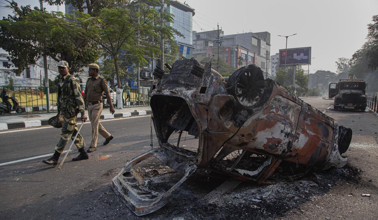 Policemen in Gauhati, India, pass a car burnt during a protest against the Citizenship Amendment Bill (CAB). Photo: AP