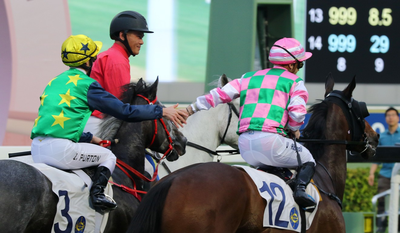 Zac Purton (left) high-five's Umberto Rispoli (right) after his final ride in Hong Kong.