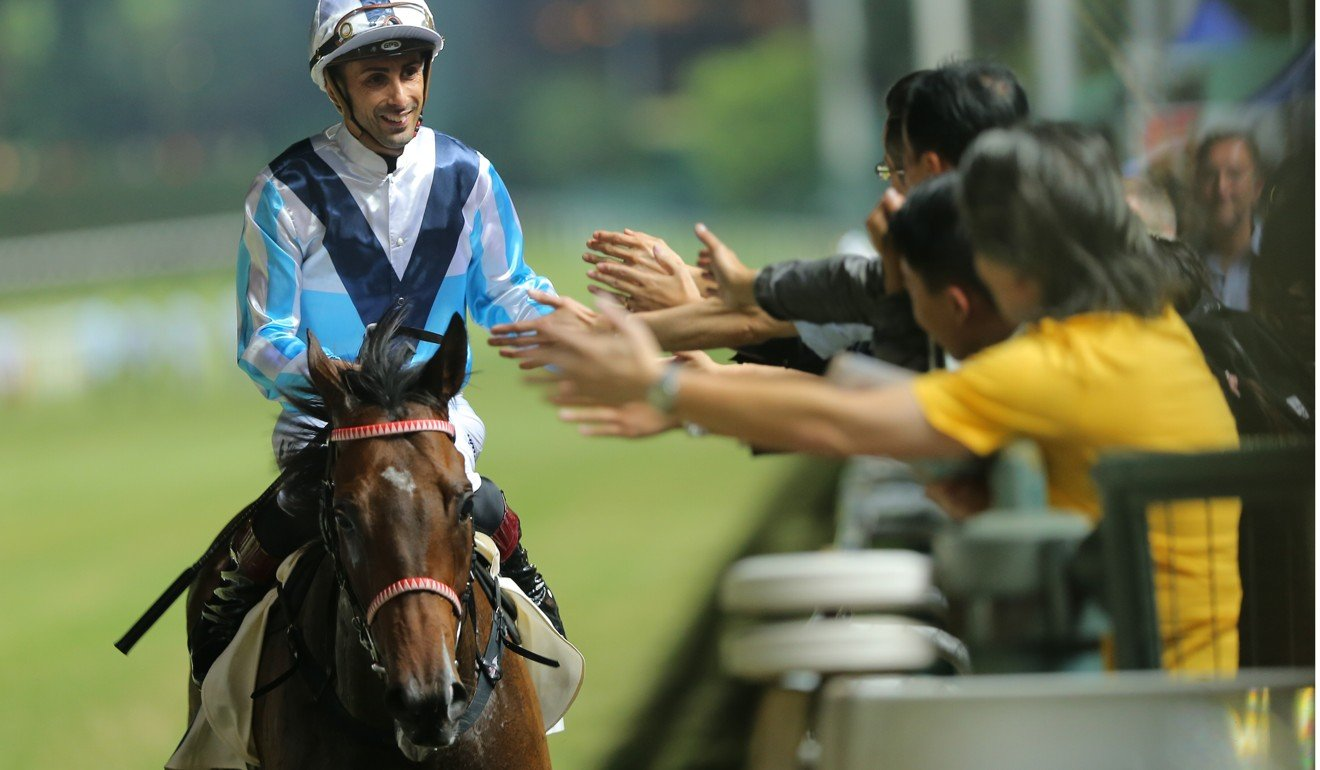 Alberto Sanna celebrates a win with fans at Happy Valley.