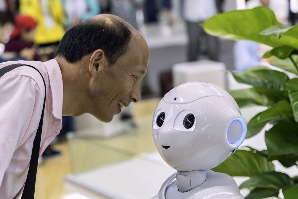 An attendee looks at a CloudMinds Technology Cloud Pepper semi-humanoid robot at the World Artificial Intelligence Conference (WAIC) in Shanghai in August. Photo: Bloomberg