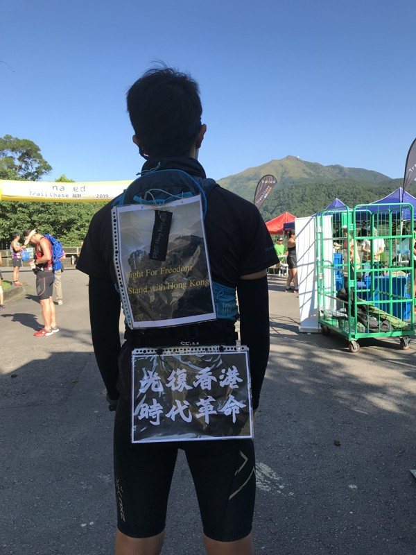 A trail runner adds his voice to the trail running scene, but wearing anti-government slogans during the Ferei Dark 45km trail running race. Photo: Mary Hui