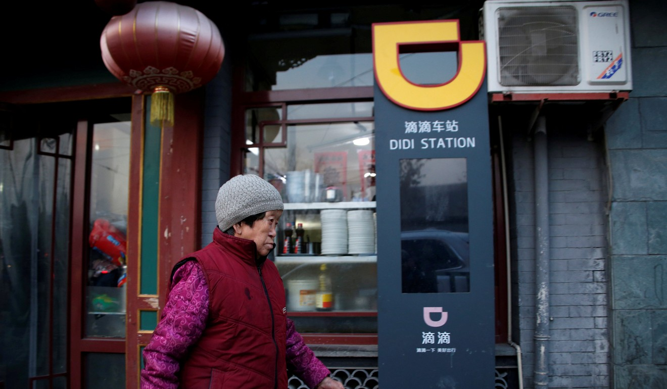 A woman walks past a sign for Didi Chuxing in Beijing, China January 2, 2019. Photo: Reuters
