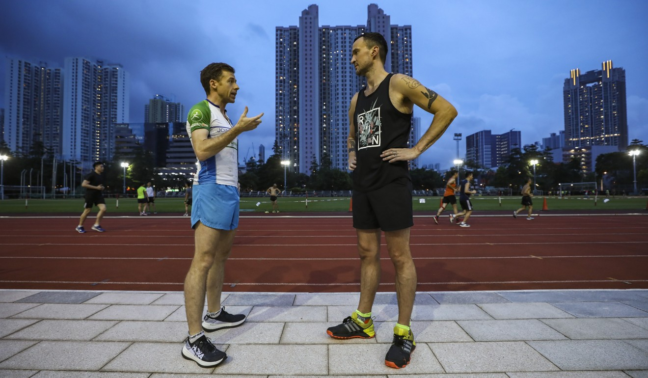 SCMP reporter Patrick Blennerhassett (right) works out with runner Jeff Campbell. By publicly sharing his marathon goals online, Blennerhassett holds himself accountable. Photo: Jonathan Wong