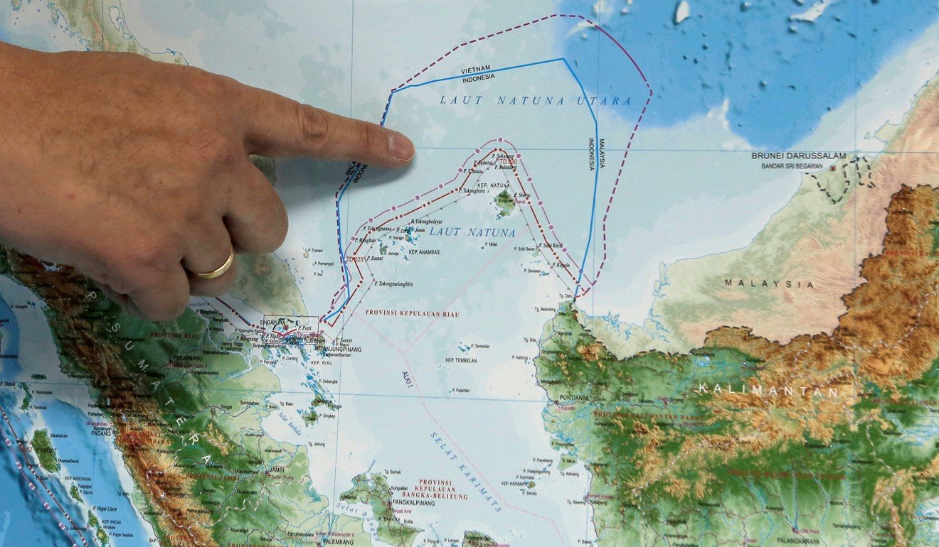 An Indonesian government official points out the area of the Natuna islands on a map. Photo: Reuters