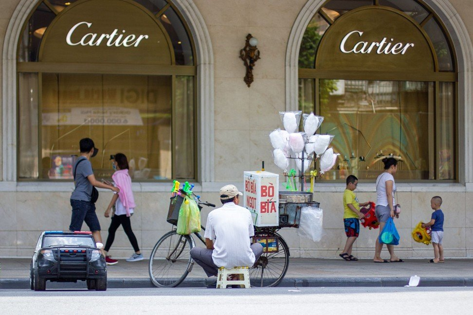 A street vendor selling a dessert outside a Cartier boutique in Hanoi's Old Quarter. Photo: Chris Humphrey