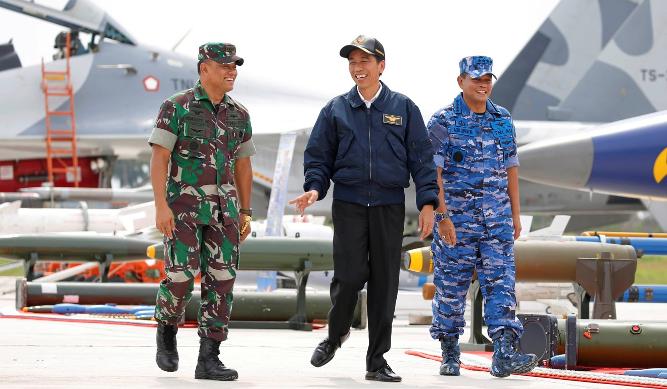 Indonesian President Joko Widodo walks past fighter jets and weapons during a military exercise on Natuna Island. Photo: AFP