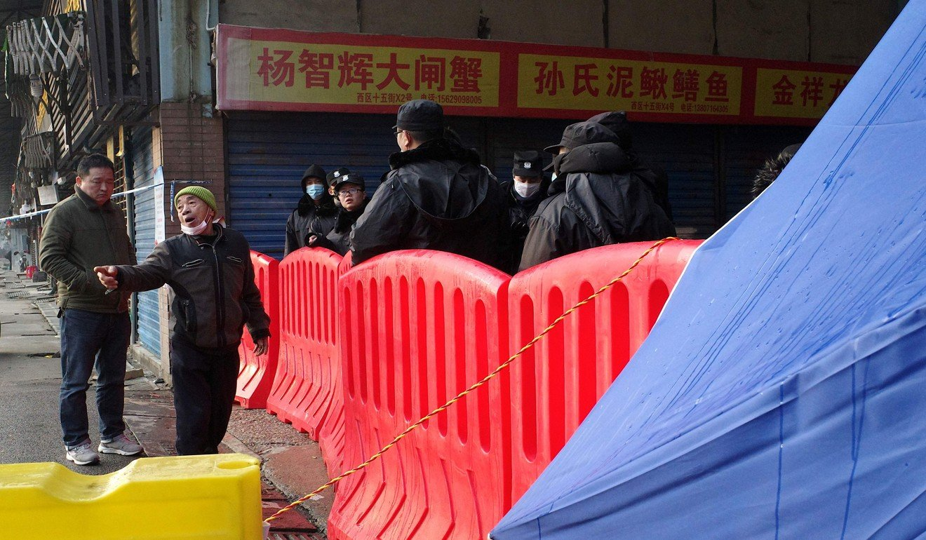 A store owner argues with security guards as he attempts to enter the closed Huanan wholesale seafood market in Wuhan recently. Photo: AFP