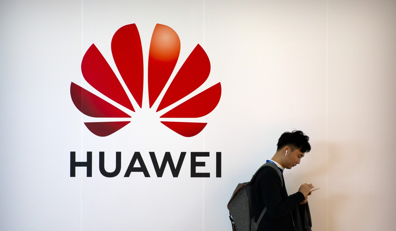 A man uses his smartphone in front of a sign for Chinese technology firm Huawei. Photo: AP
