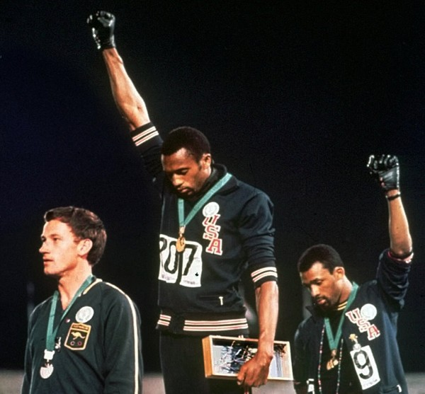Australian silver medallist Peter Norman, left, stands on the podium as Americans Tommie Smith (centre) and John Carlos raise their gloved fists in a black power protest in 1968. Photo: Associated Press