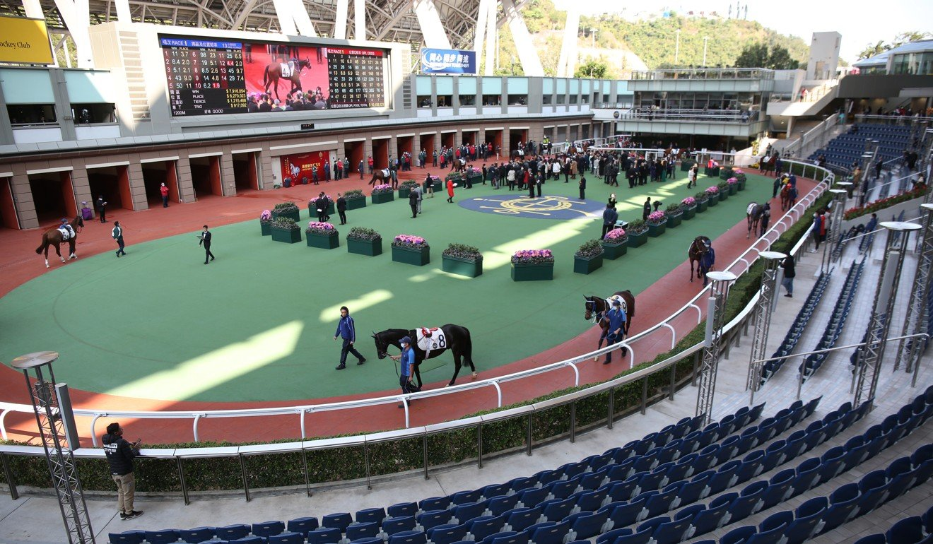 Connections of horses in the opening race at Sha Tin mingle in front of the empty stands. Photo: Kenneth Chan