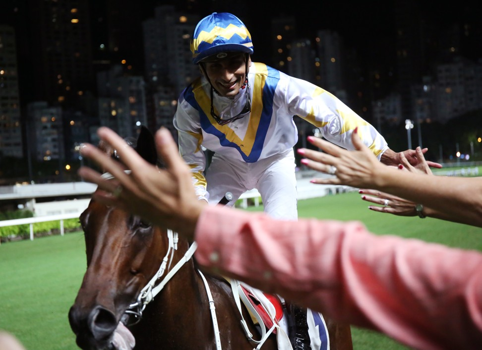 Karis Teetan high-fives fans after winning aboard Hong Kong Bet.