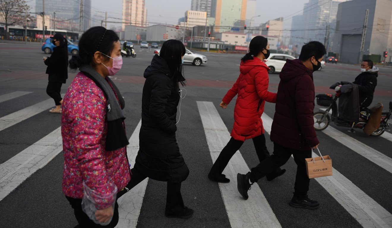 People wear face masks as they cross a normally busy street in Beijing on Tuesday. Photo: AFP