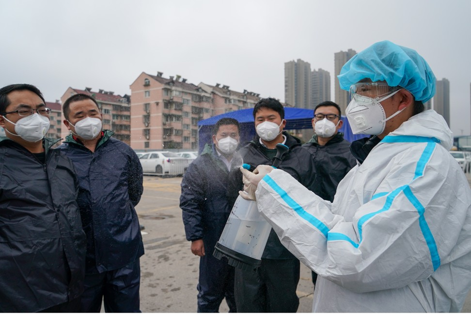 A staff member of Didi Chuxing teaches drivers how to use a spray bottle to disinfect their cars in Nanjing, in eastern China's Jiangsu province, on February 14. Photo: Xinhua