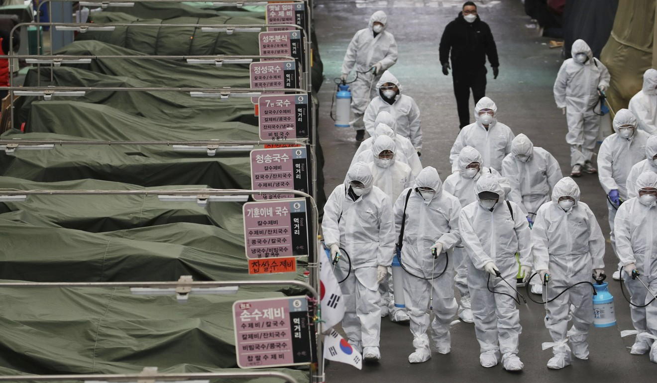 Workers in protective gear disinfect a market in the South Korean city of Daegu on February 23 as a preventive measure amid the city's Covid-19 outbreak. Photo: AFP